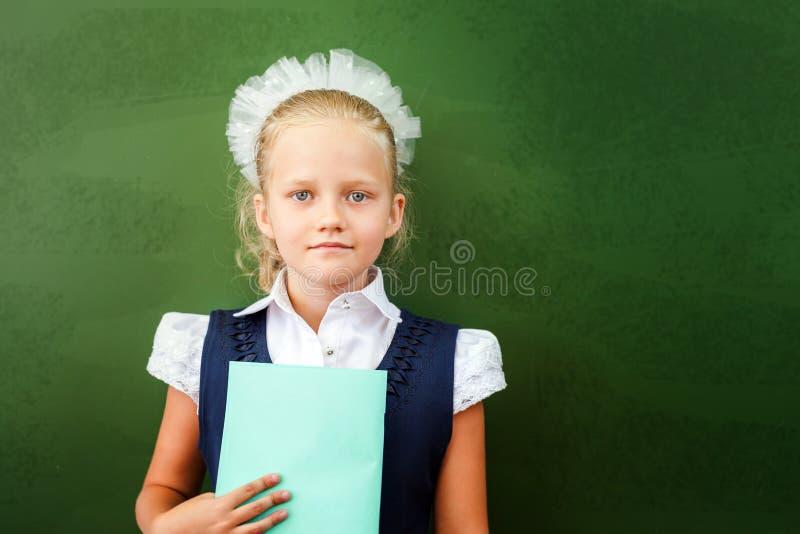 Estudante de primeiro grau que guarda o caderno perto do quadro-negro na sala de aula imagem de stock royalty free