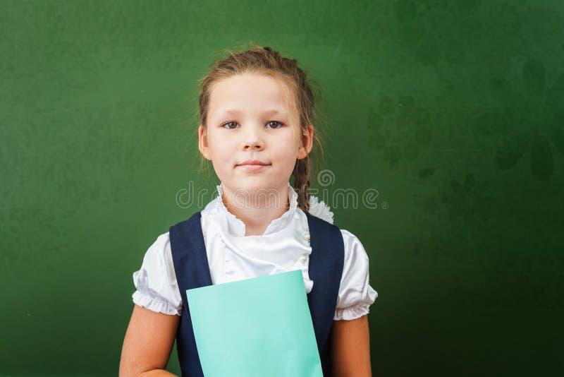 Estudante de primeiro grau que guarda o caderno perto do quadro-negro na sala de aula imagens de stock royalty free