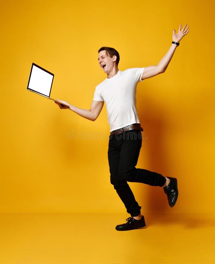 Estudante de salto com port?til imagem de stock royalty free