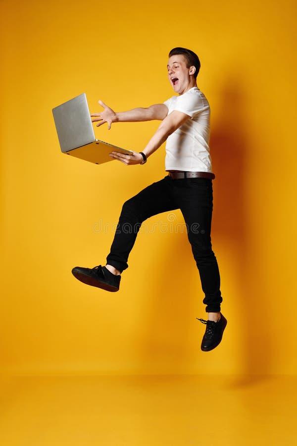 Estudante de salto com port?til imagens de stock
