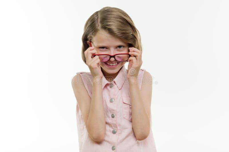 Estudante de sorriso bonita nos vidros no fundo branco, isolado Criança de sorriso que olha na câmera com seus vidros para baixo imagem de stock