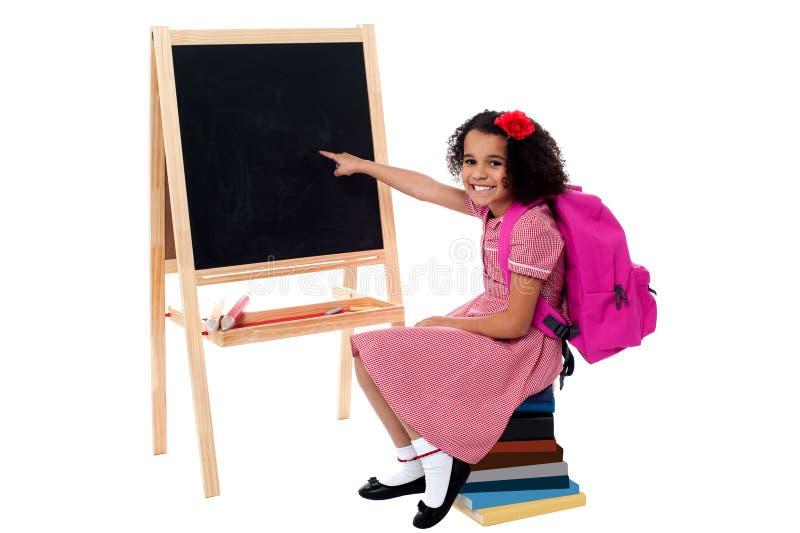 Estudante de sorriso bonito que aponta no quadro vazio fotografia de stock