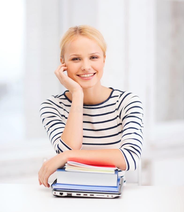 Estudante de sorriso com portátil, livros e cadernos imagem de stock