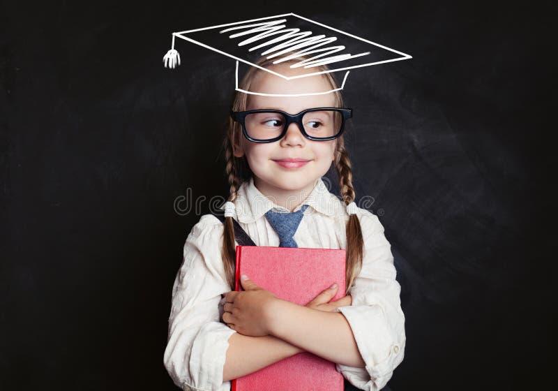 Estudante de sorriso da estudante com livro e chapéu da graduação imagem de stock