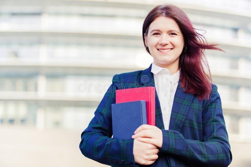 Estudante de sorriso novo seguro que guarda fora livros fotografia de stock royalty free