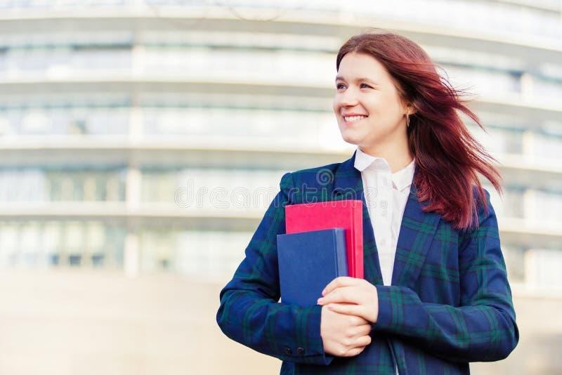 Estudante de sorriso novo seguro que guarda fora livros fotografia de stock