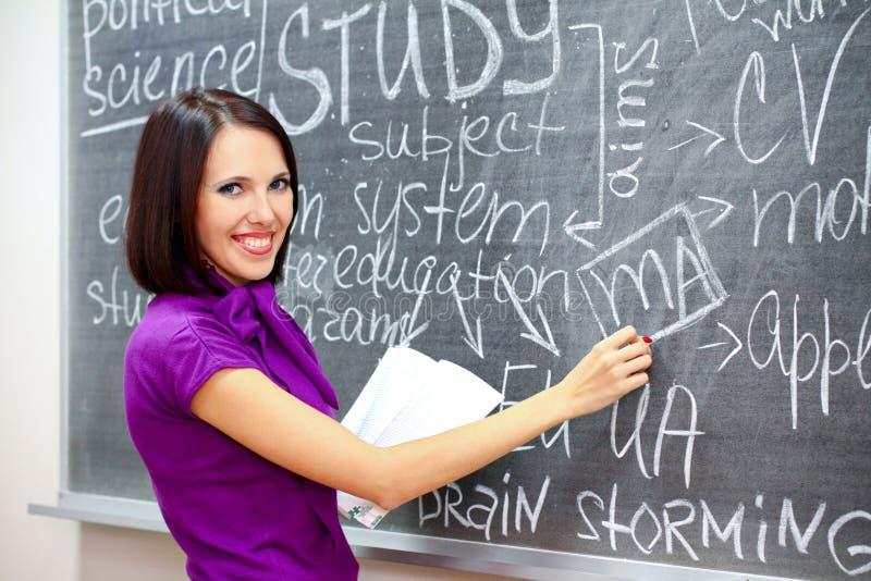 Estudante de sorriso perto do quadro-negro imagem de stock royalty free