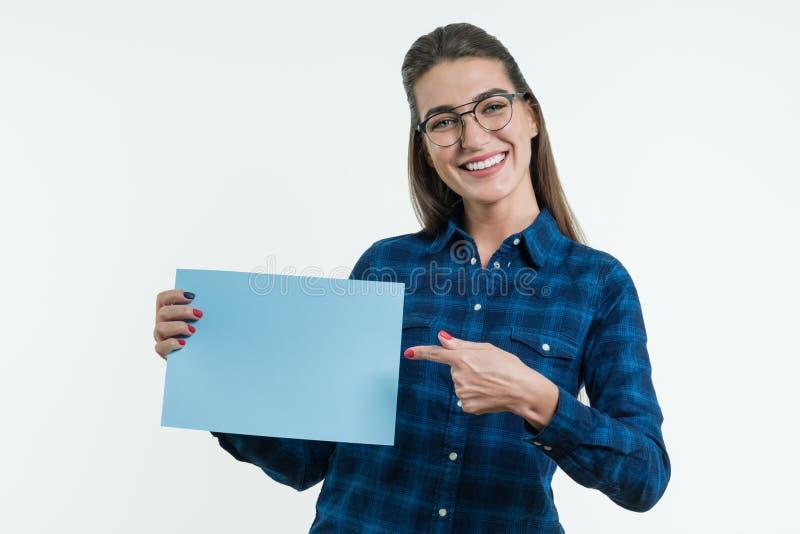 Estudante de sorriso positiva que guarda uma folha limpada do papel azul, apontando um dedo no papel imagens de stock