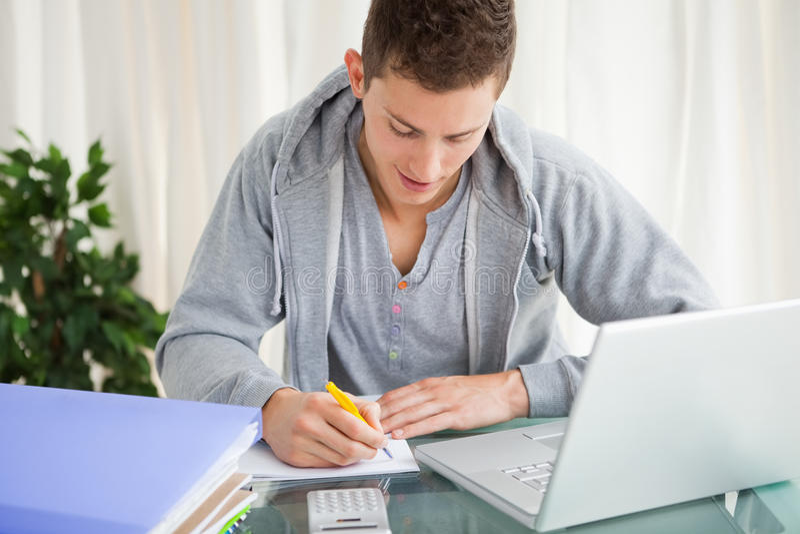 Estudante de sorriso que faz seus trabalhos de casa com um portátil foto de stock royalty free