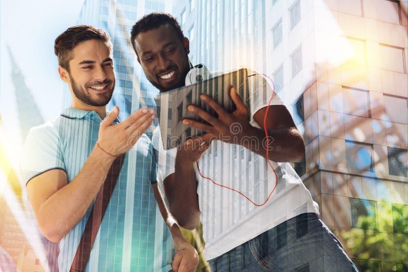 Estudante de sorriso que guarda uma tabuleta moderna quando seu amigo que olha a fotografia de stock