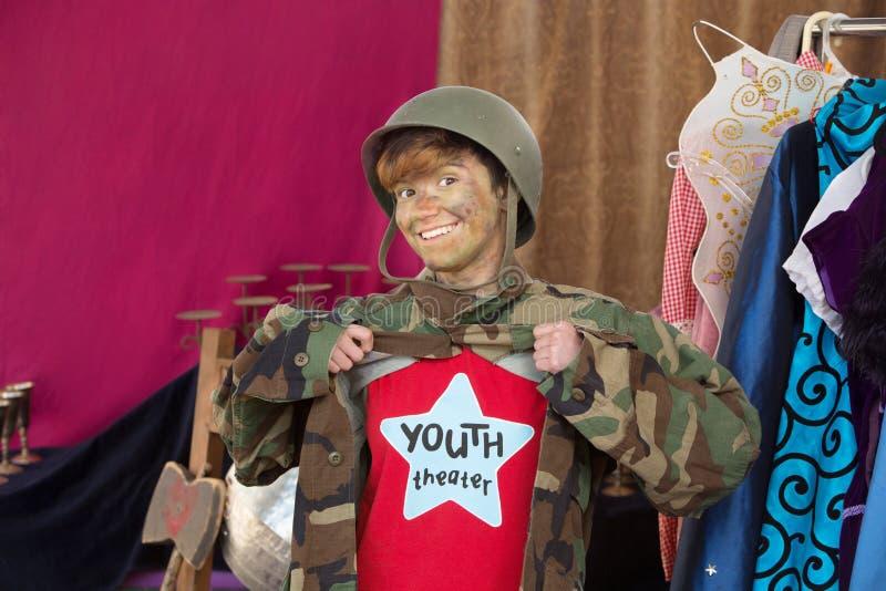 Estudante de sorriso vestido como o homem do exército fotografia de stock