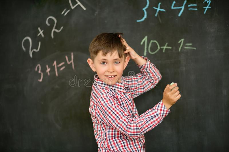 A estudante decide na placa o problema com o giz e pensa sobre a solução, risca sua cabeça imagem de stock
