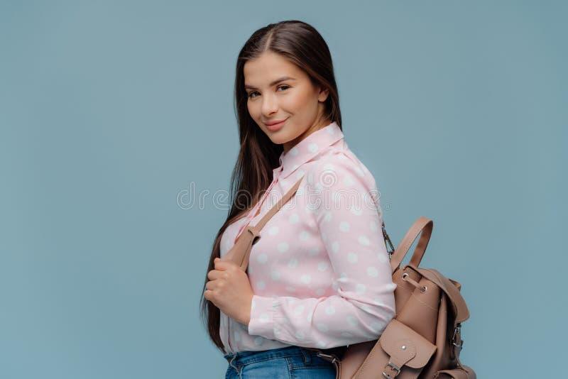 A estudante deleitada elegante leva a mochila, retorna da escola, indo ter classes extra, veste a camisa do às bolinhas, olha fotografia de stock royalty free