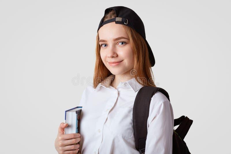 A estudante deleitada eyed azul guarda o livro, leva a trouxa, veste o tampão preto, indo à biblioteca, lê-o e os cramms materiai fotografia de stock royalty free