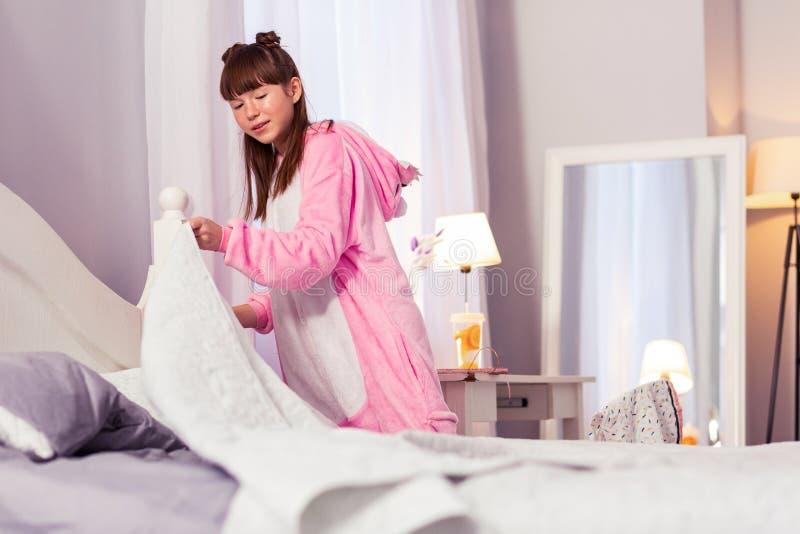Estudante deleitada positiva que prepara sua cama para o sono imagem de stock