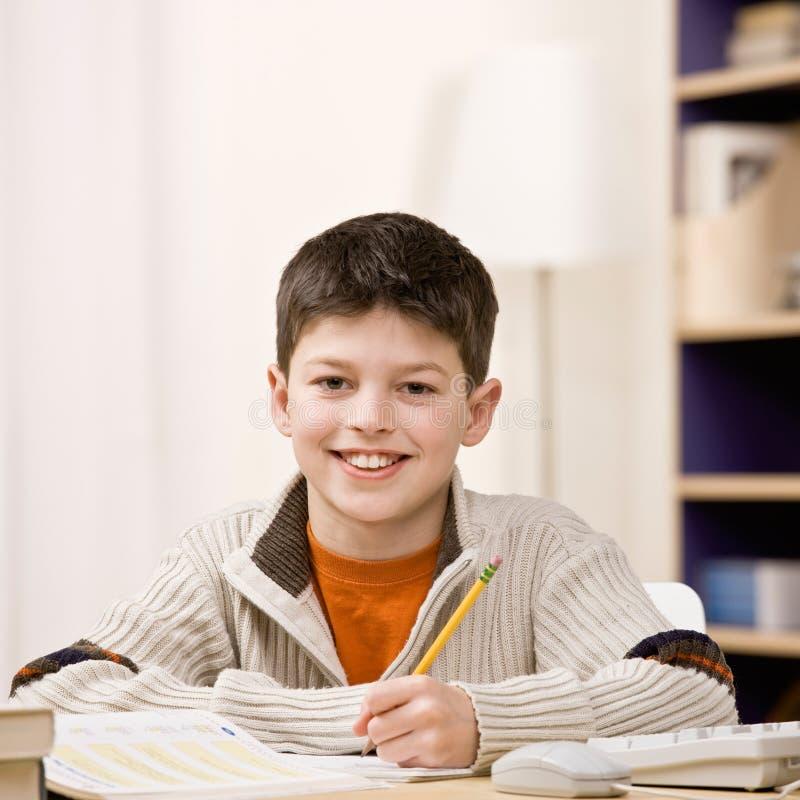 Estudante determinado que faz trabalhos de casa imagem de stock