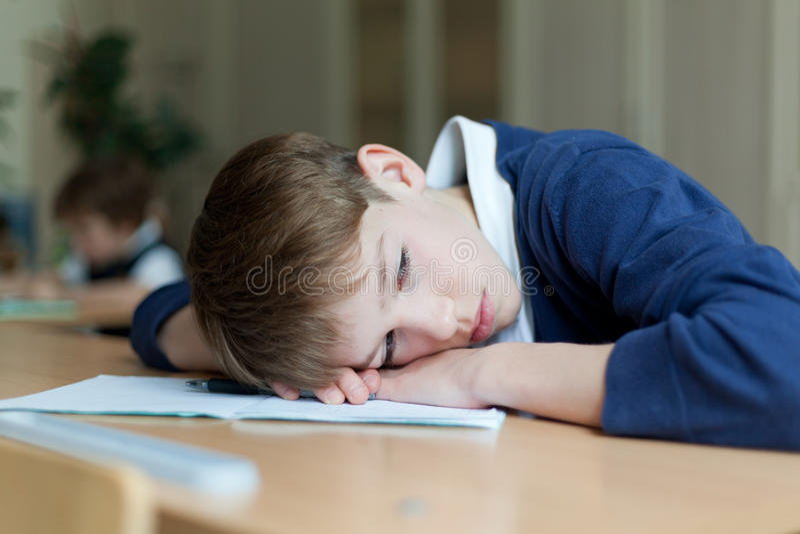 Estudante diligente que senta-se na mesa, sala de aula fotos de stock