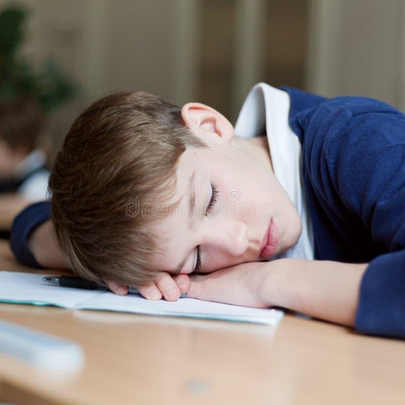 Estudante diligente que senta-se na mesa, sala de aula fotografia de stock royalty free
