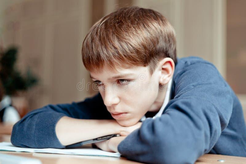 Estudante diligente que senta-se na mesa, sala de aula foto de stock royalty free