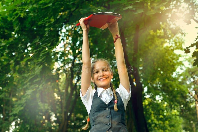 Estudante do estudante feliz com as tranças no uniforme que guarda livros nas mãos em cima imagem de stock royalty free