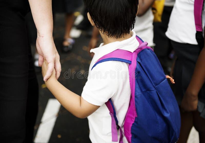 Estudante do jardim de infância que guarda as mãos com adulto imagem de stock royalty free
