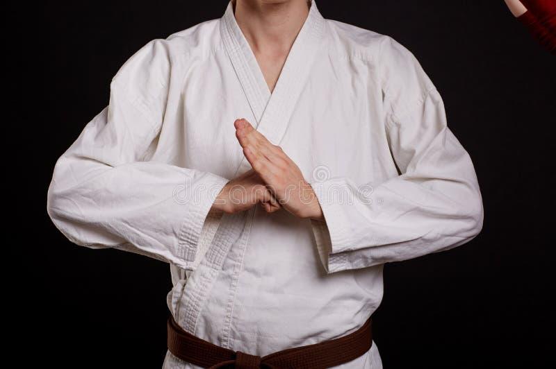 Estudante do karaté do close-up em um fundo preto Lutador no sinal de ruptura mostrando uniforme Conceito das lições do karaté foto de stock