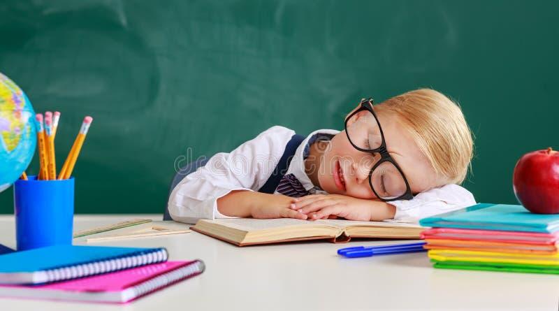 Estudante do menino da estudante da criança cansado, adormecido sobre o quadro-negro da escola fotografia de stock royalty free