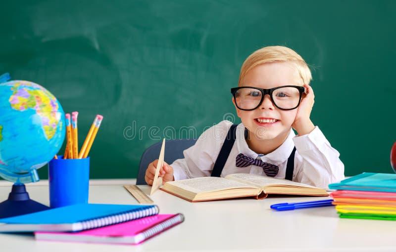 estudante do menino da estudante da criança sobre o quadro-negro da escola imagem de stock royalty free