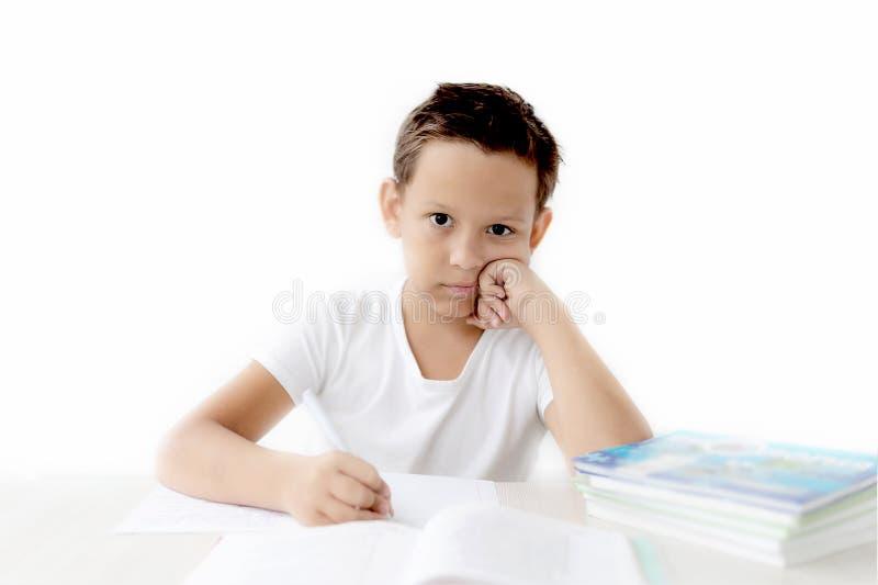 A estudante do menino ensina lições que escreve no caderno foto de stock