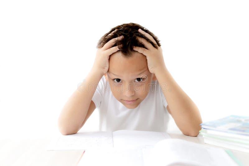 A estudante do menino ensina lições que escreve no caderno fotos de stock