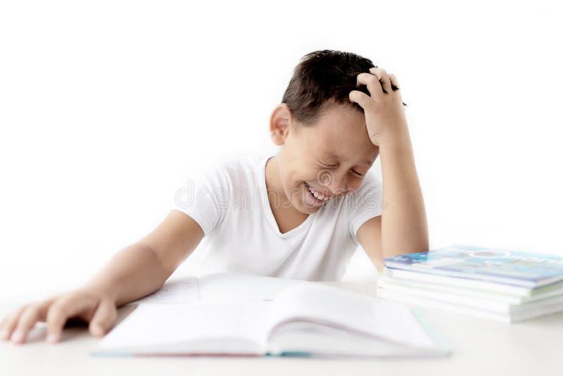 A estudante do menino ensina lições que escreve no caderno fotografia de stock royalty free
