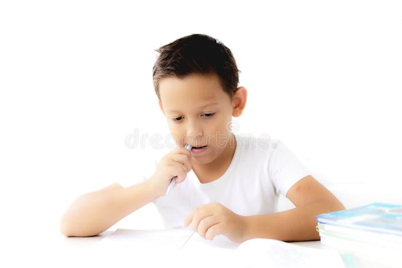 A estudante do menino ensina lições que escreve no caderno imagens de stock royalty free