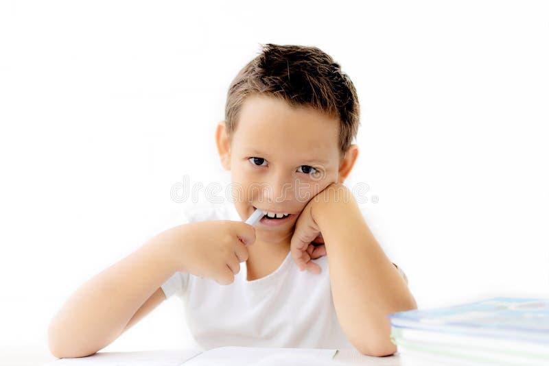 A estudante do menino ensina lições que escreve no caderno imagem de stock