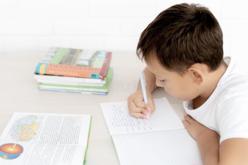 A estudante do menino ensina lições que escreve no caderno e nos livros de leitura imagem de stock