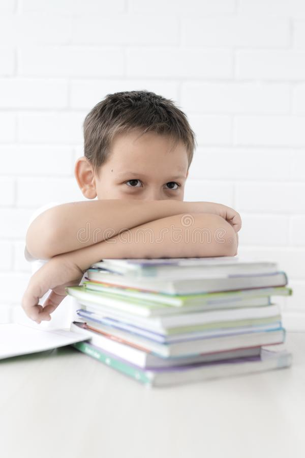 A estudante do menino ensina lições que escreve no caderno e nos livros de leitura fotografia de stock