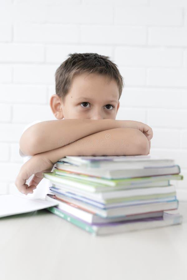 A estudante do menino ensina lições que escreve no caderno e nos livros de leitura fotografia de stock royalty free