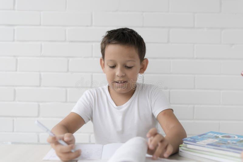 A estudante do menino ensina lições que escreve no caderno e nos livros de leitura fotos de stock royalty free