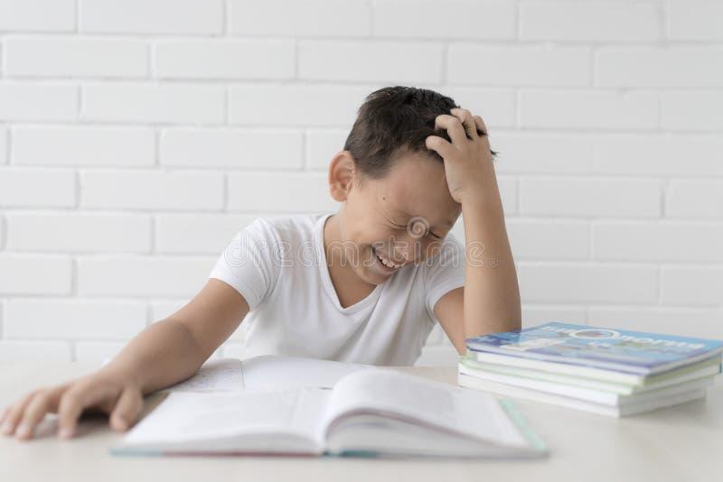 A estudante do menino ensina lições que escreve no caderno e nos livros de leitura foto de stock