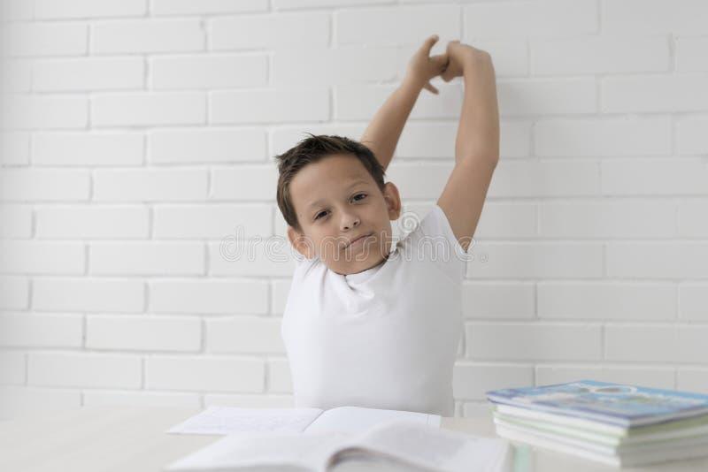 A estudante do menino ensina lições que escreve no caderno e nos livros de leitura imagens de stock
