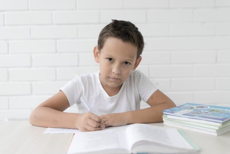 A estudante do menino ensina lições que escreve no caderno e nos livros de leitura imagem de stock royalty free