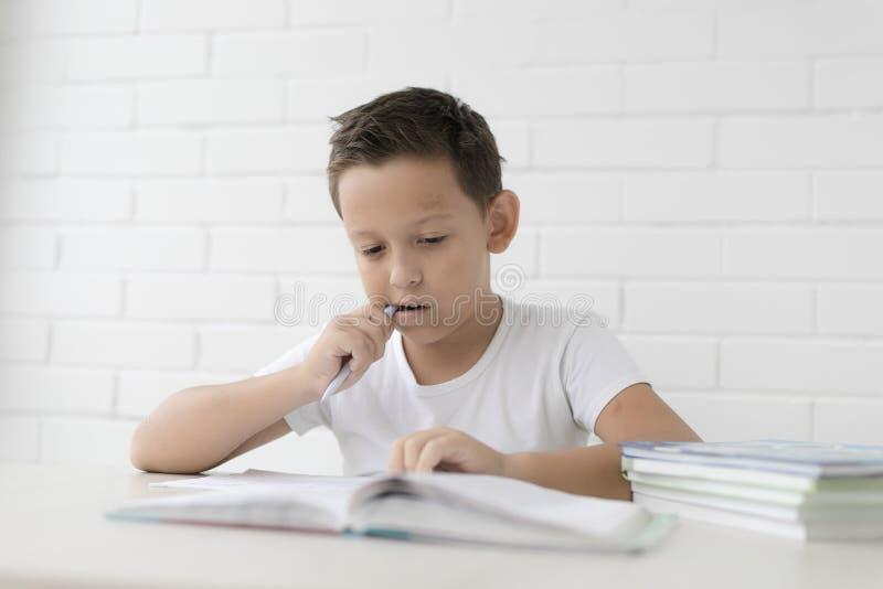A estudante do menino ensina lições que escreve no caderno e nos livros de leitura imagens de stock royalty free