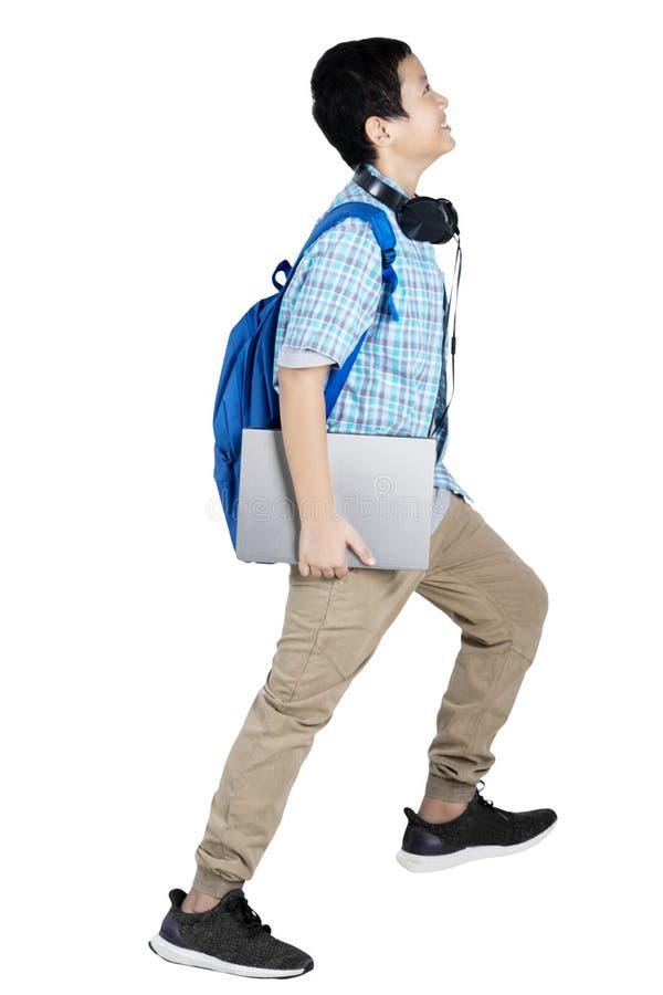 Estudante do menino do Preteen que leva um portátil no estúdio imagens de stock royalty free