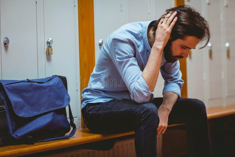 Estudante do moderno que sente triste no corredor imagem de stock