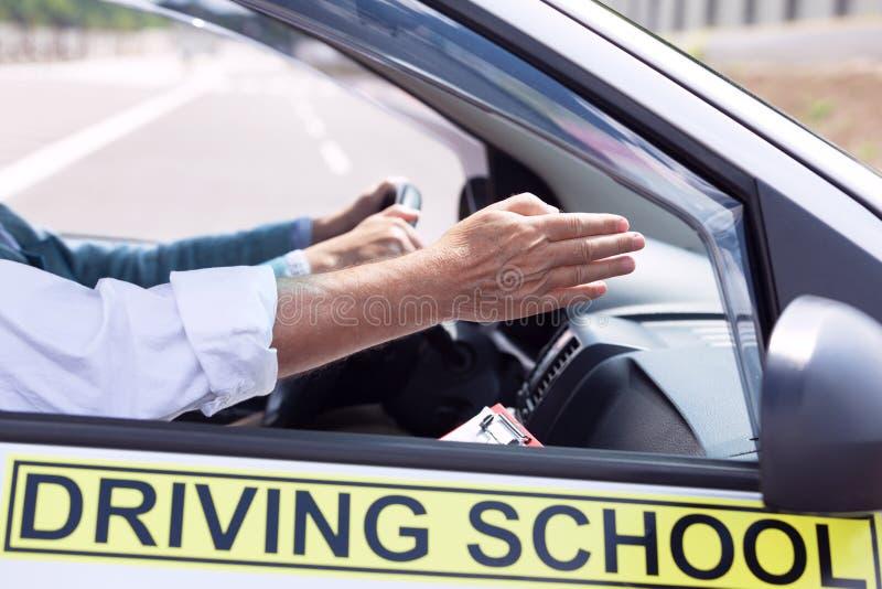 Estudante do motorista do principiantes que conduz o carro com instrutor foto de stock