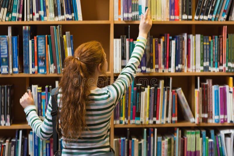 Estudante do ruivo que toma o livro da prateleira superior na biblioteca fotos de stock