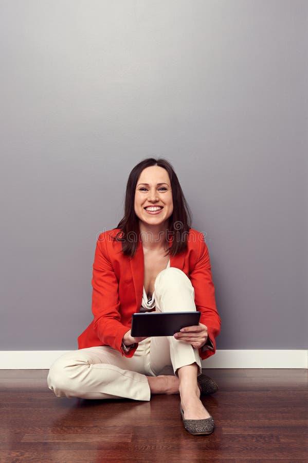 Estudante do smiley que senta-se no assoalho foto de stock royalty free