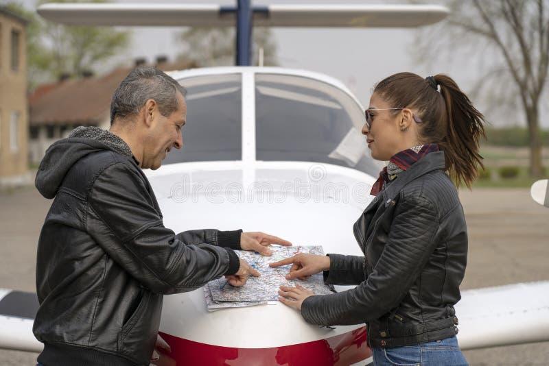 Estudante e piloto Discussing Flight Route sobre uma carta da aviação fotografia de stock