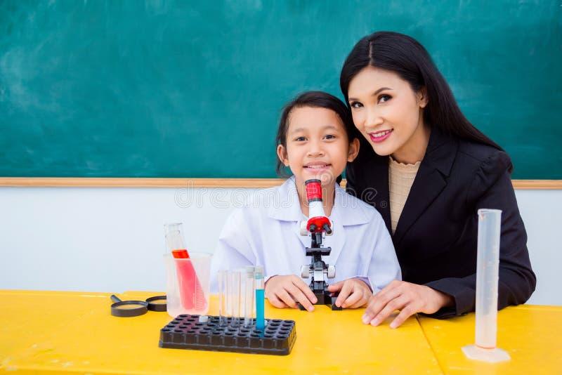 Estudante e professor bonito que sentam-se na sala de aula fotos de stock royalty free