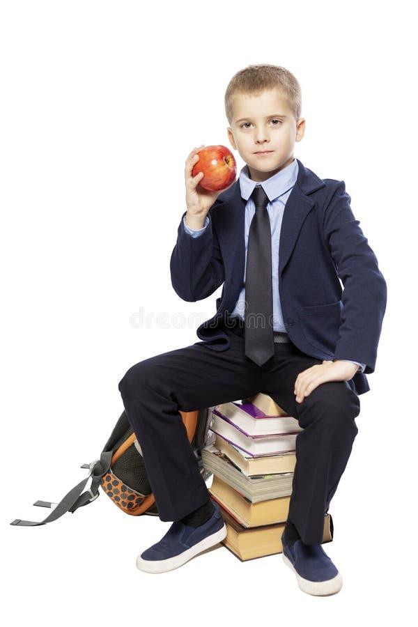 Estudante em um terno com uma maçã em sua mão que senta-se nos livros Isolado em um fundo branco fotografia de stock royalty free