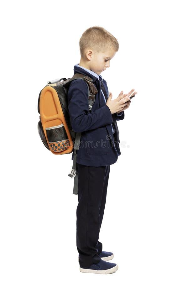 Estudante em um terno com uma trouxa e um smartphone em suas mãos Vista lateral Isolado em um fundo branco imagens de stock royalty free